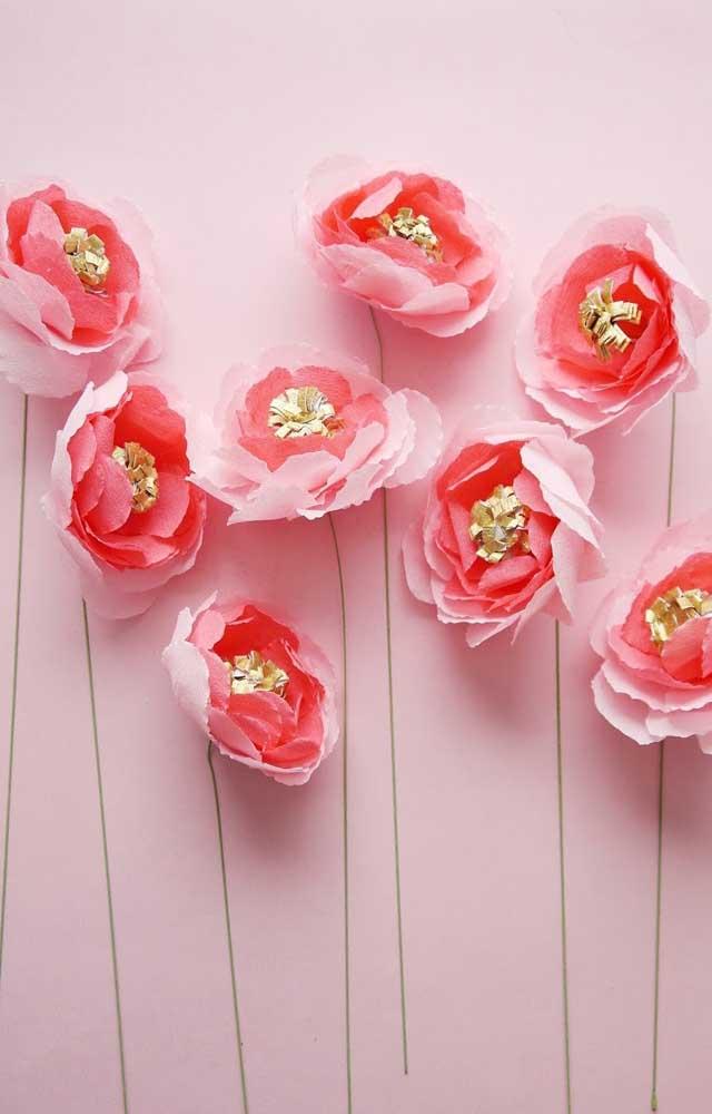 Flores de papel crepom cor de rosa com miolo dourado ajudando a destacar as pétalas