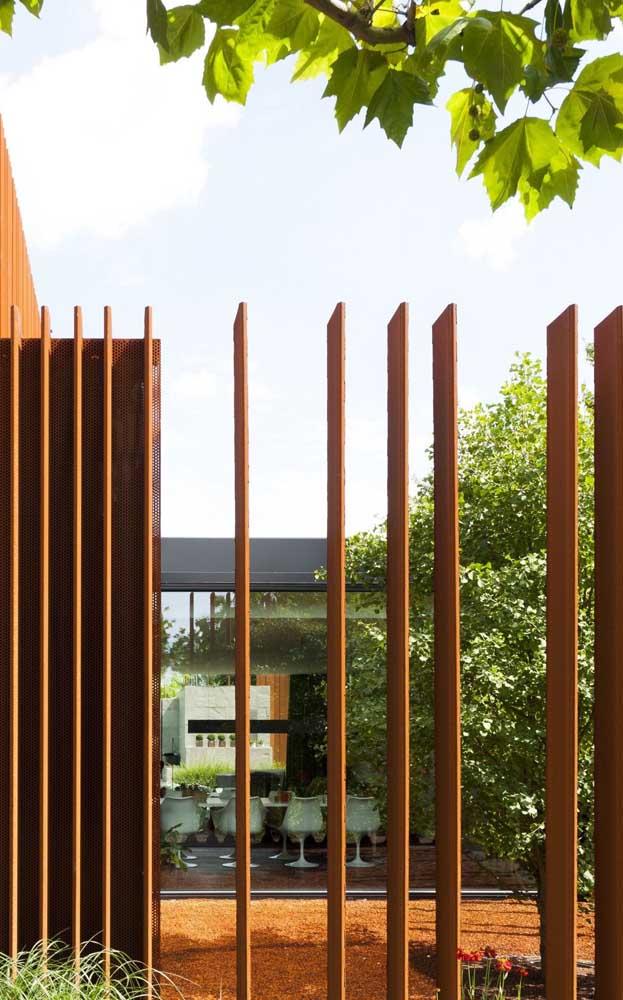 """Cerca de madeira para jardim com design contemporâneo e ripas instaladas """"de lado"""", perfeitas para causar sensação de ambiente fechado, dependendo da perspectiva que se olha"""