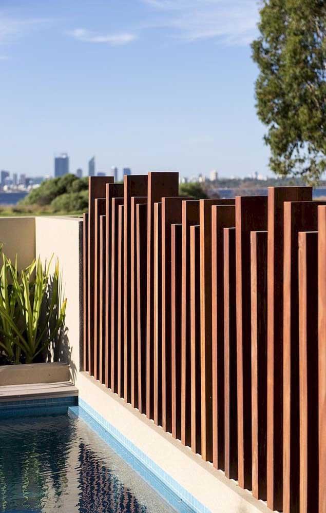 Essa cerca de madeira para a piscina se destaca pela originalidade com que as ripas foram instaladas