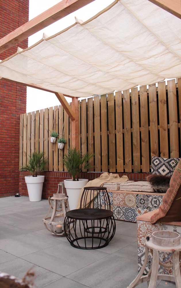 A varanda rústica, convidativa e simples ficou perfeita com a cerca de madeira ao fundo