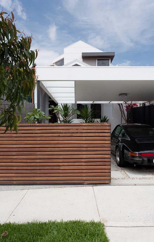 A fachada da casa ganhou uma cerca de madeira elegante, com ripas na horizontal e com altura considerável para manter a privacidade do local