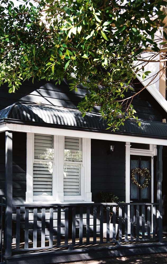 Nessa outra casa, a cerca de madeira foi pintada para combinar com o acabamento em preto e branco da fachada