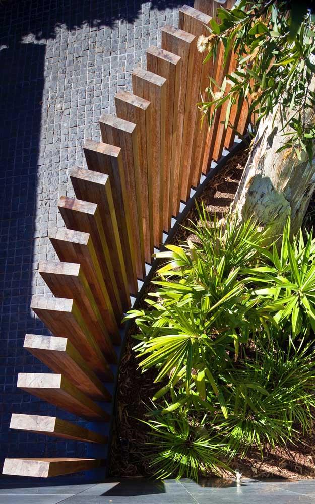 Vista de cima de uma cerca de madeira sem estrutura horizontal, com ripas de espessura mais grossa e que acompanham a alvenaria do muro
