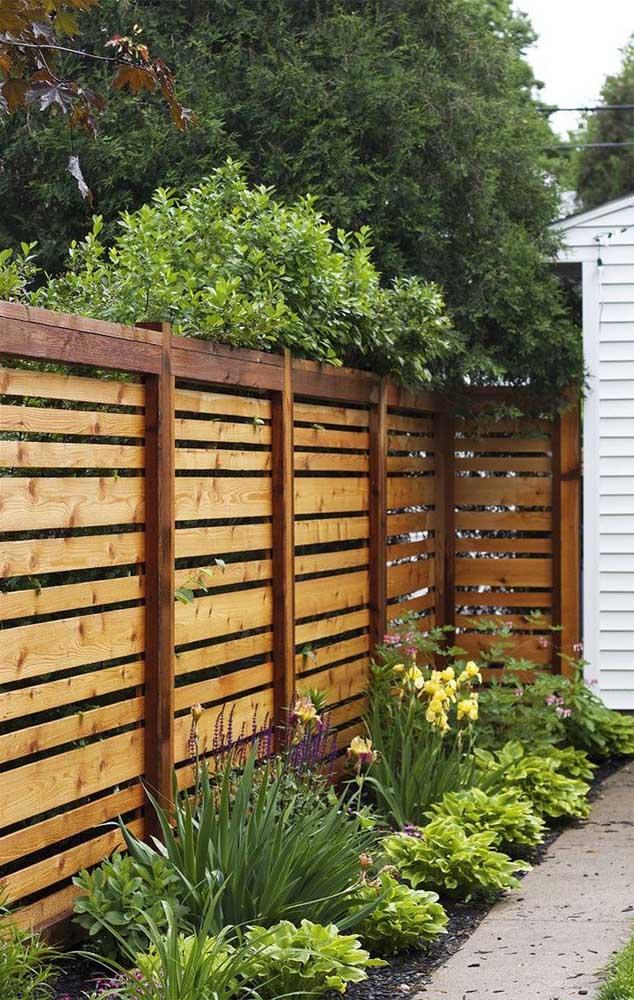 Vista interna da cerca de madeira com acabamento nas bordas e ripas colocadas na horizontal para demarcar o terreno do imóvel