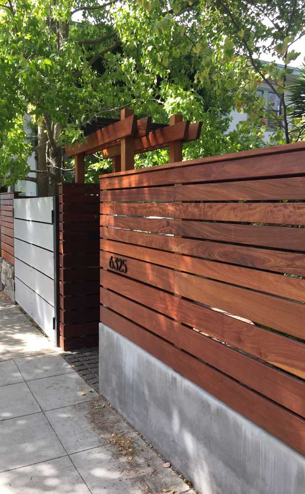 Modelo de cerca de madeira instalada sobre o muro de alvenaria na entrada da casa
