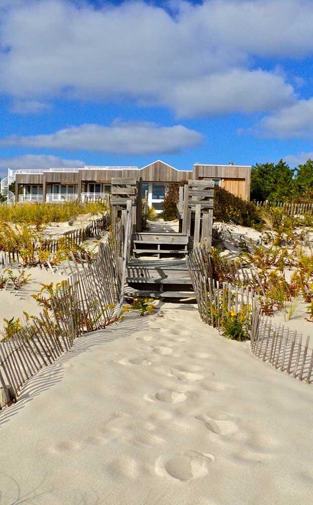 O acesso privativo da casa de praia ganhou uma trilha envolta pela cerca de madeira simples e rústica