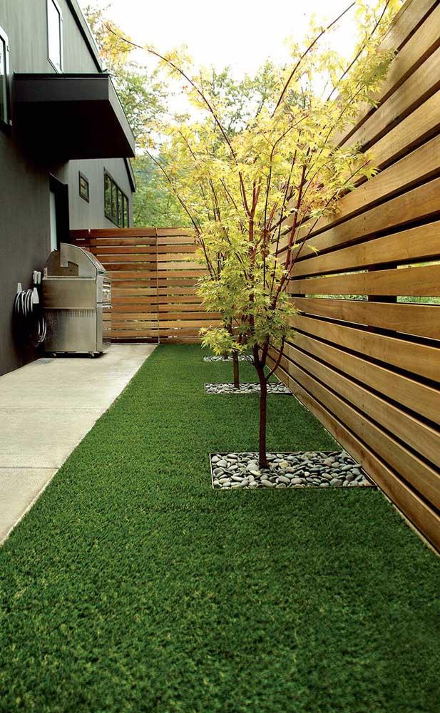 O pequeno jardim e área de churrasco da casa ganhou a privacidade da cerca de madeira