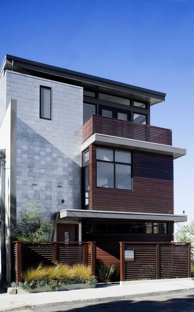 Aqui, o mesmo estilo de madeira foi escolhido para a cerca da fachada, para a varanda e para o acabamento no segundo andar da casa