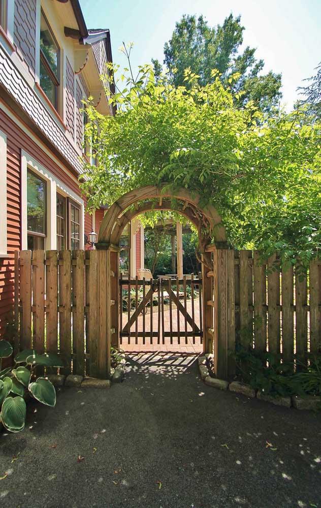 Uma entrada cheia de verde complementada pela cerca de madeira