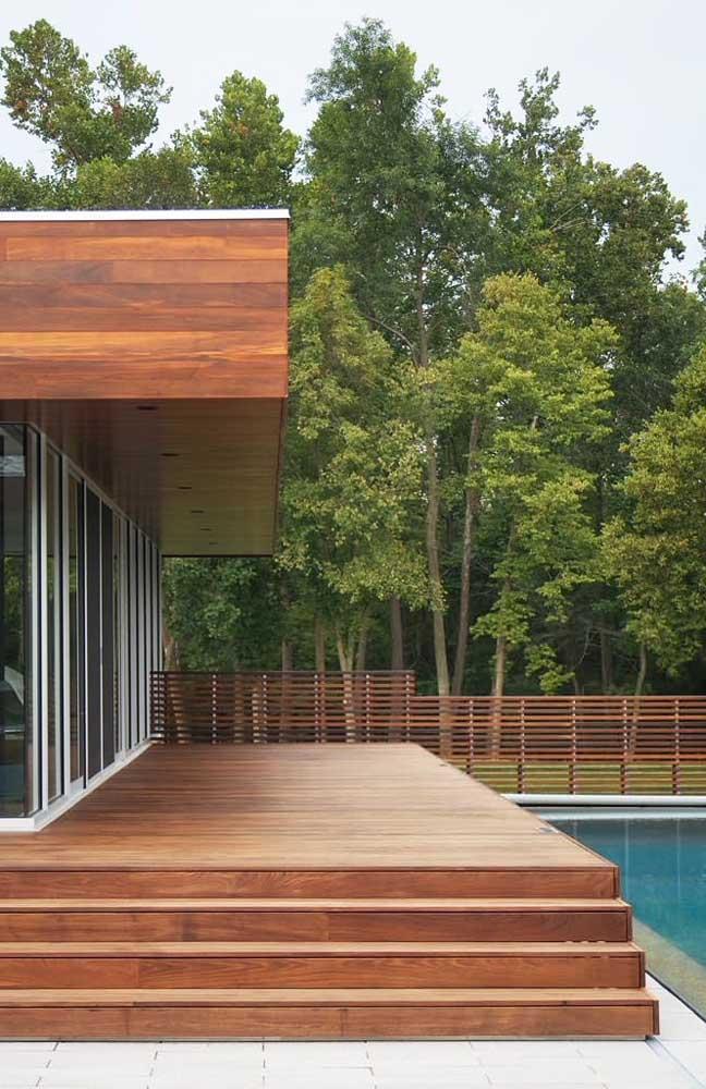 Cerca de madeira baixa para a piscina, delimitando o espaço externo da casa