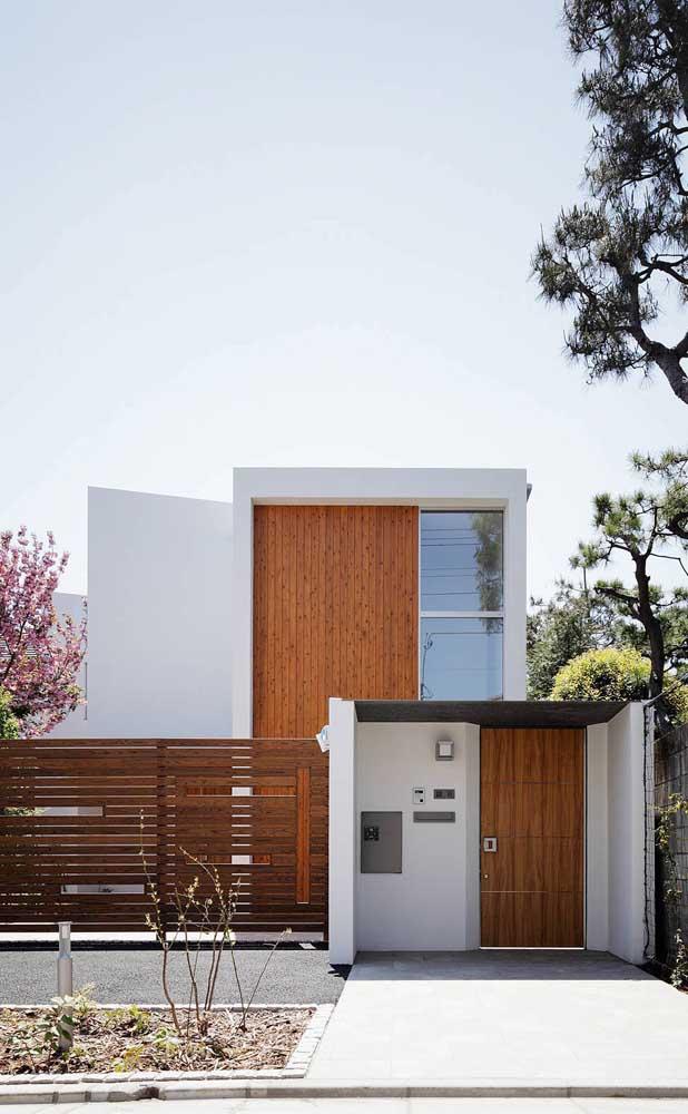 Essa casa com design contemporâneo apostou no uso da cerca de madeira para a fachada