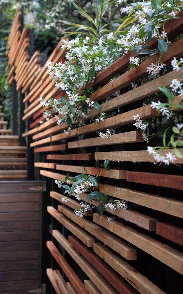 Um modelo diferente e criativo para montar a cerca de madeira; repare que os vãos entre as ripas permitem a passagem das flores