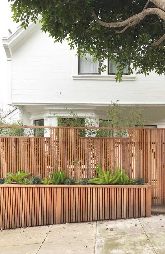 Cerca de madeira com ripas finas para a fachada da casa clássica