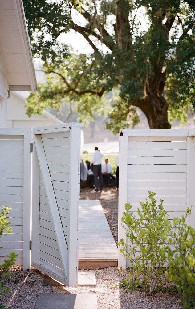 Cerca de madeira branca para a entrada da residência