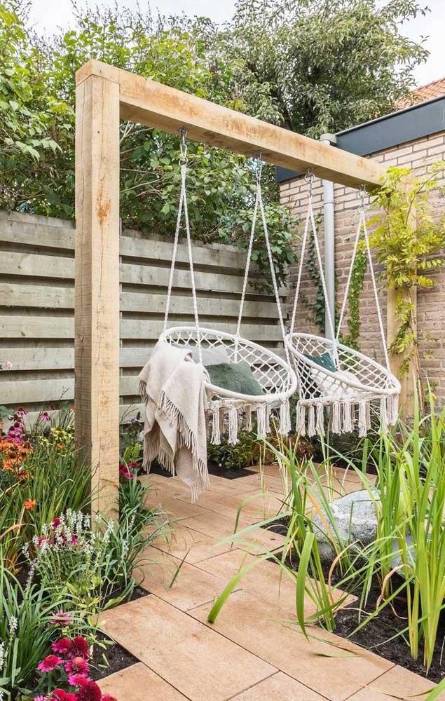 O espaço aconchegante e convidativo no jardim ficou ainda mais bonito com a cerca de madeira ao fundo