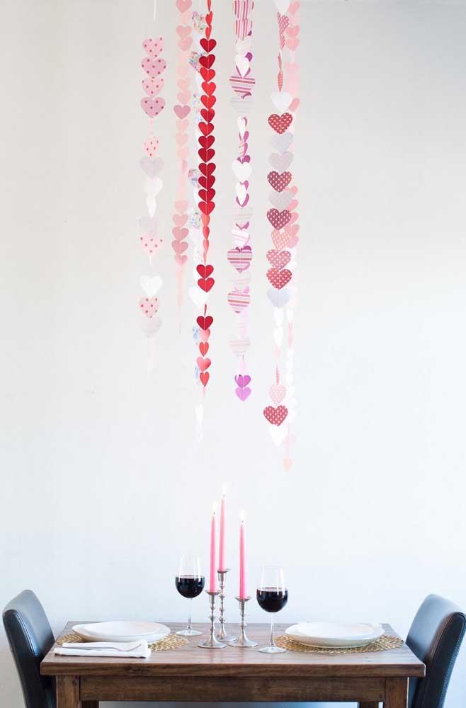 Para decorar a mesa do jantar romântico, foi utilizada uma cortina de corações de papel. Opção criativa, simples e barata