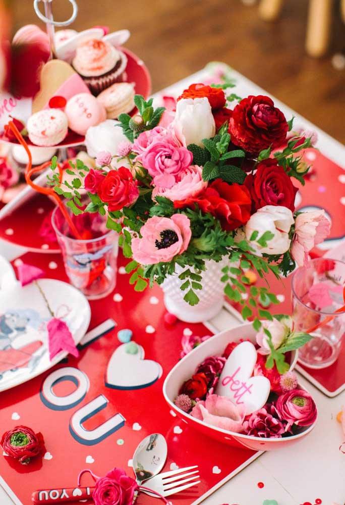 Um belo arranjo de flores vermelhas não pode faltar na mesa do jantar.