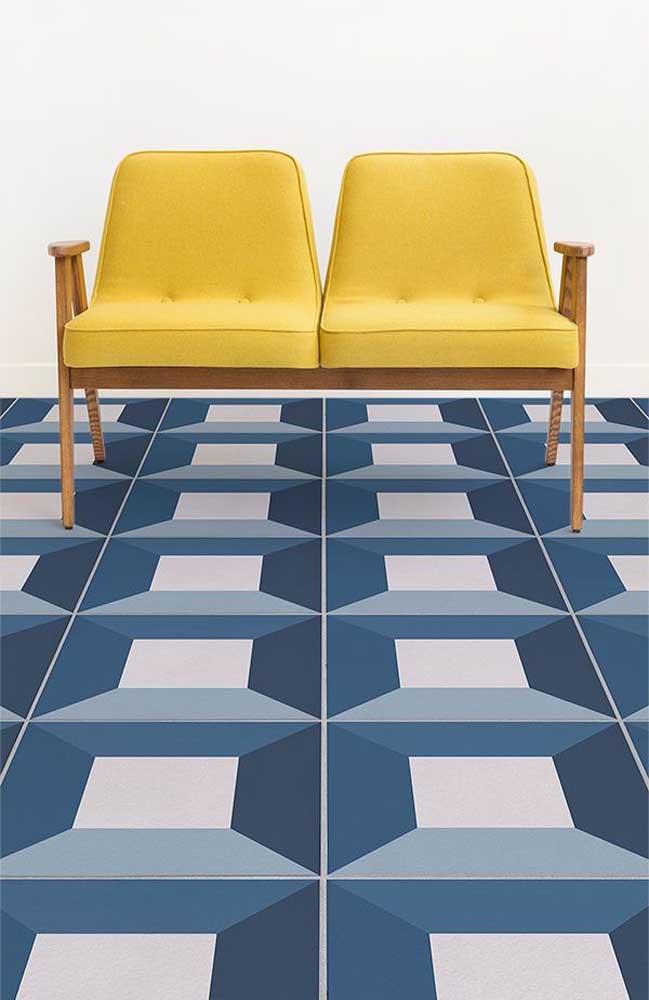 Piso 3D geométrico com efeito de profundidade; a poltrona amarela ajuda a realçar a cor do piso