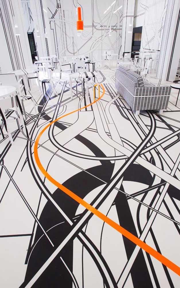 """Super conceitual, esse ambiente contemporâneo investiu em um piso 3D preto e branco cheio de linhas e com um traço laranja para """"animar"""" o espaço"""