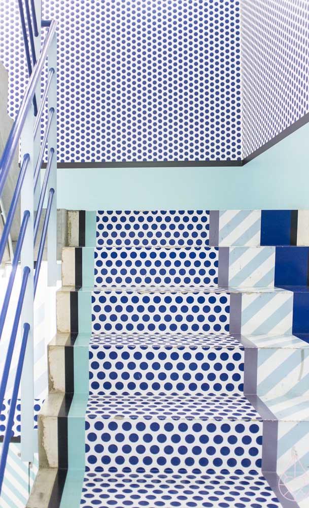 Diferentes padrões geométricos no piso 3D acompanham essa escada até alcançar a parede aos fundos