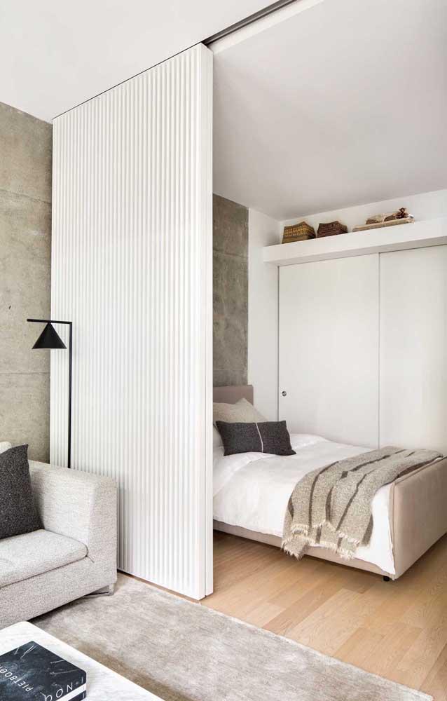 Esse quarto de casal pequeno faz integração com a sala de estar; para dividir os ambientes, um painel de madeira de correr