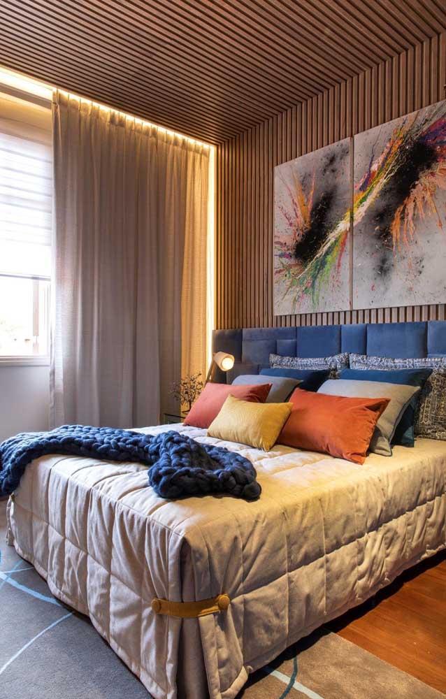 Cores quentes, madeira e uma iluminação indireta dão o toque de conforto e aconchego nesse quarto de casal pequeno
