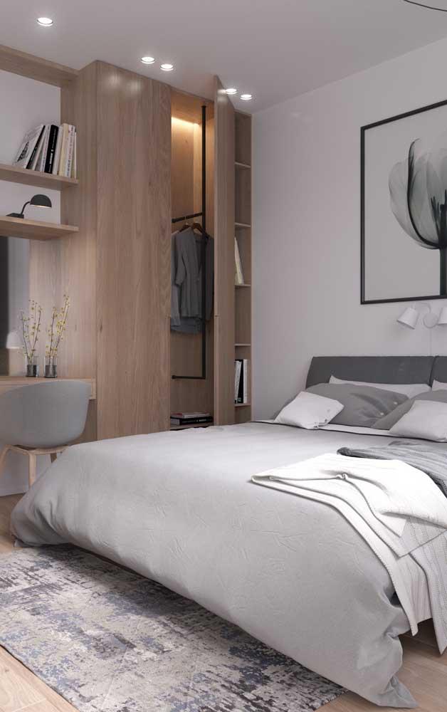 Quarto de casal pequeno com móveis planejados; a cama recebeu uma grande atenção no ambiente