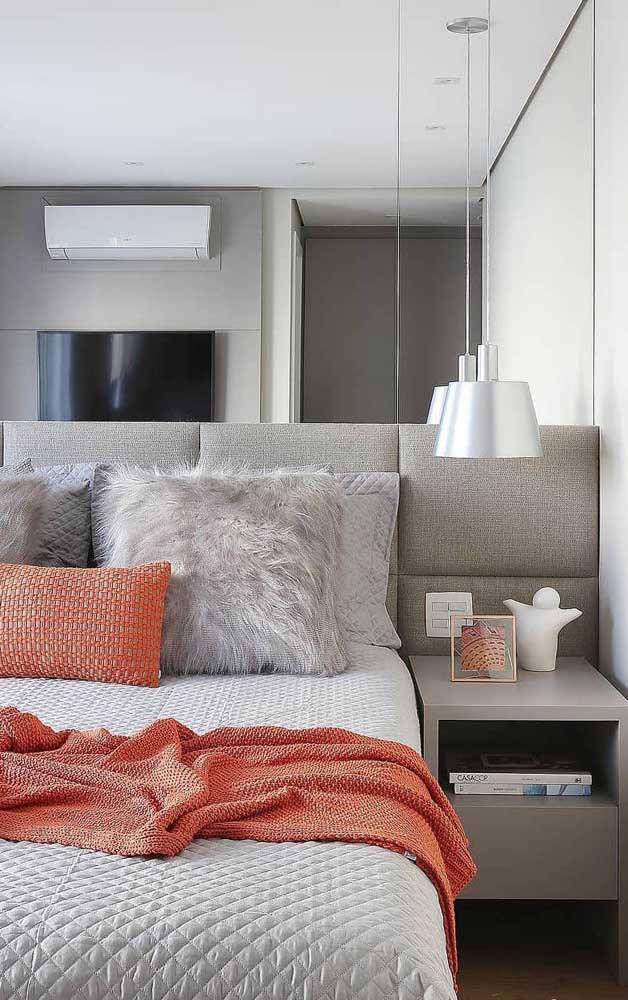 O espelho na parede da cabeceira ajuda a ampliar visualmente o quarto de casal
