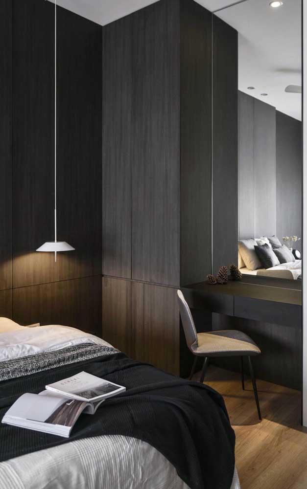Os móveis escuros garantem um tom intimista ao quarto do casal; repare que a escrivaninha se ajustou perfeitamente ao local