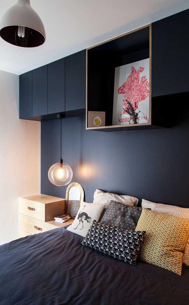 O tom de azul profundo do armário combinado a iluminação difusa garantem o clima acolhedor desse quarto pequeno de casal