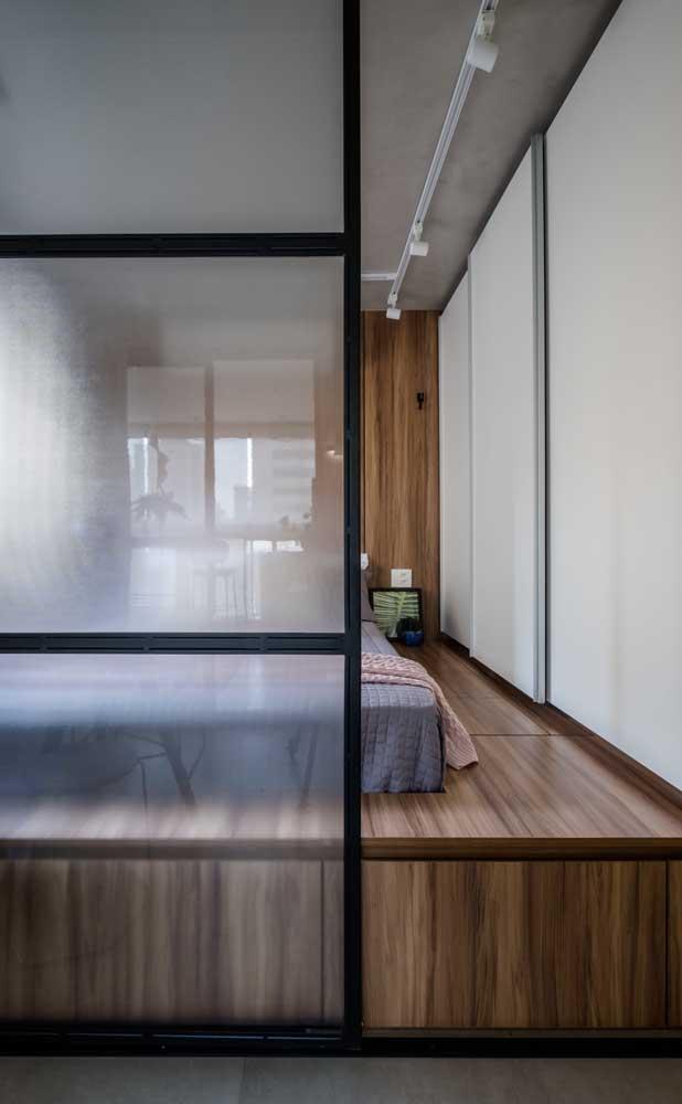 Esse pequeno quarto de casal ganhou uma estrutura em madeira que o eleva do chão, tornando-o mais aconchegante