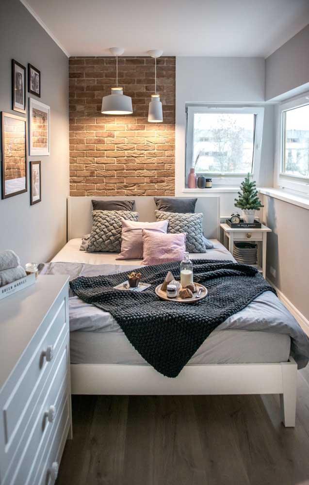 Para esse quarto de casal super pequeno a solução foi recostar a cama na parede lateral; destaque para o revestimento de tijolinho que deu um toque de aconchego a mais no ambiente