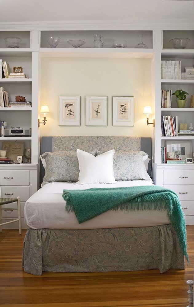 Quarto de casal pequeno com cama embutida entre os nichos e prateleiras