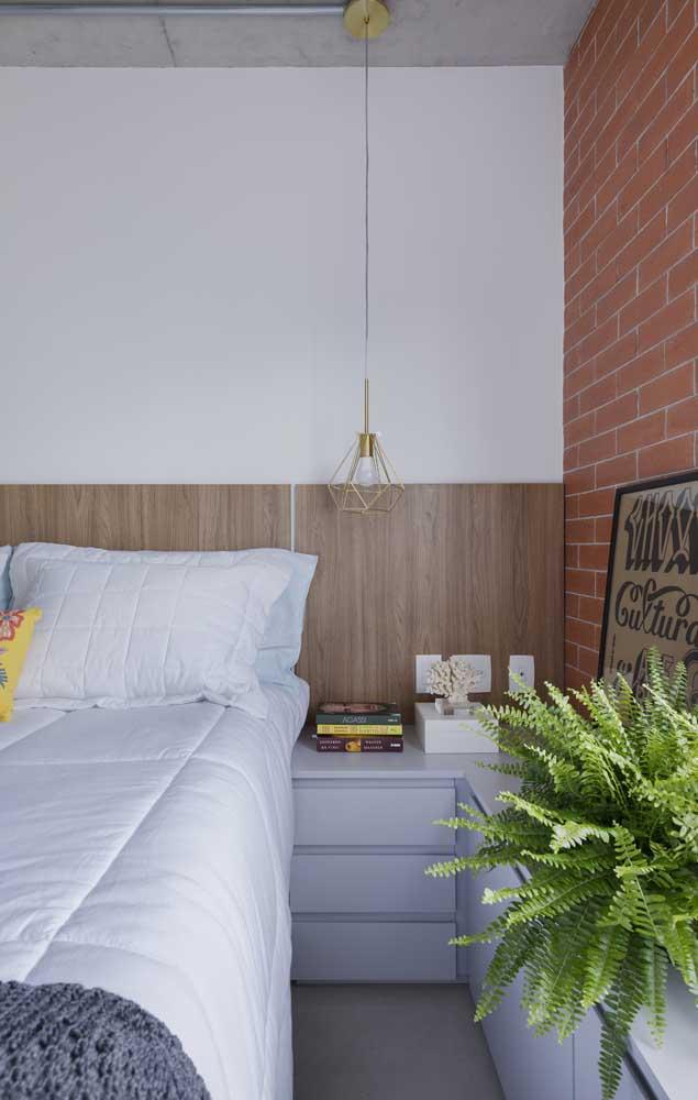 O estilo industrial também marca presença nesse quarto de casal pequeno; destaque para a samambaia trazendo verde ao ambiente