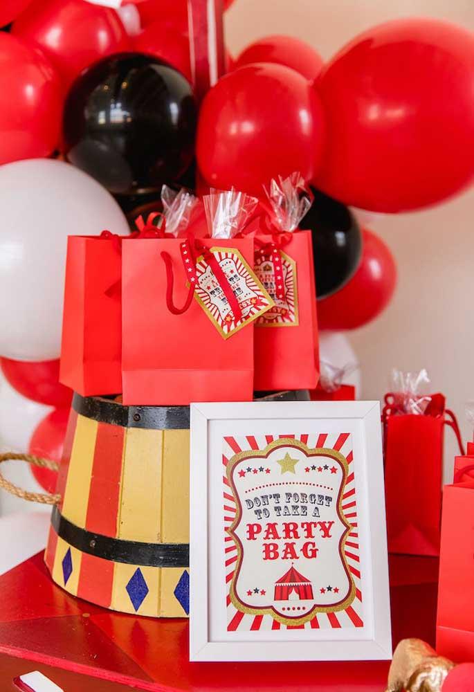 Uma boa opção de embalagem para lembrancinha circo são as sacolas vermelhas com uma etiqueta personalizada.