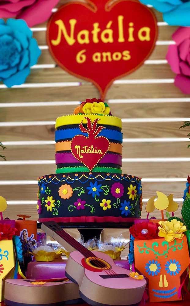 Mesa do bolo decorada com caveiras e violão; no fundo, um painel de flores de papel gigante