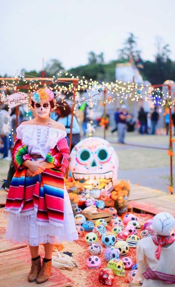 """Caveiras coloridas espalhadas pelo chão; roupa e maquiagem também seguem o tema da """"Festa no Céu"""""""