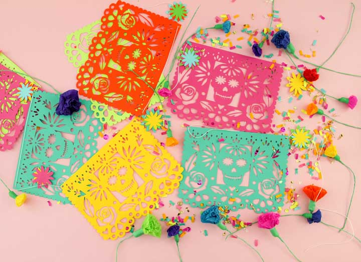 Bandeirolas e os tradicionais papéis picados mexicanos; para complementar, flores coloridas