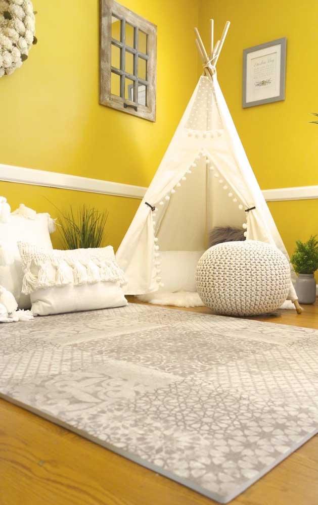 O quartinho infantil de cores quentes apostou em um tapete emborrachado branco e cinza