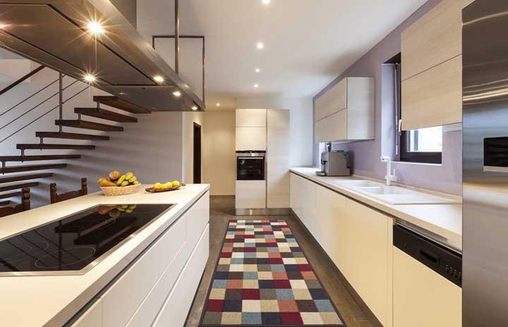 Um tapete colorido com fundo emborrachado para descontrair o visual dessa cozinha branca e clean