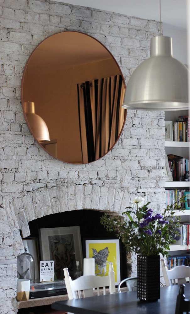 A parede rústica de tijolinhos contracenou perfeitamente com a elegância do espelho bronze redondo