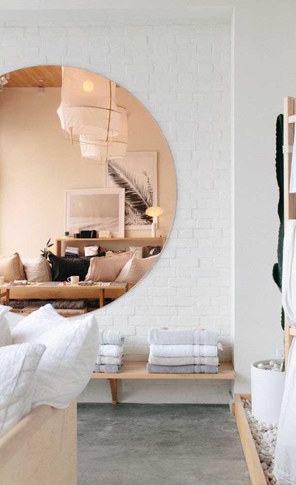 Um enorme espelho bronze redondo decora essa sala de estar em tons neutros