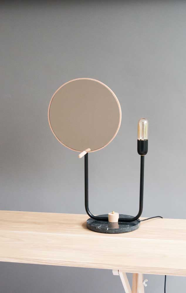 Versão mini de espelho redondo para ser usado na bancada de mesa; destaque para a luminária que o acompanha