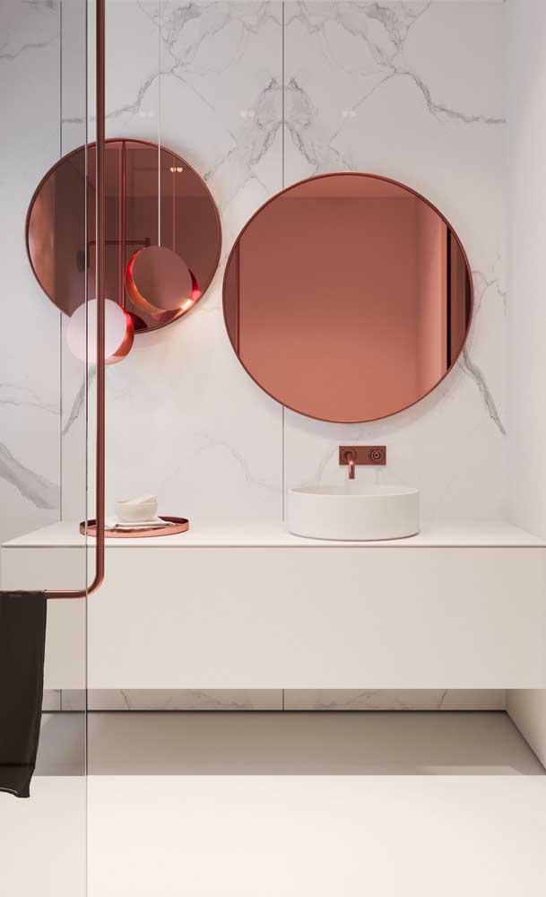 Para combinar com o luxo da parede de mármore do banheiro foram usados dois espelhos de bronze redondos