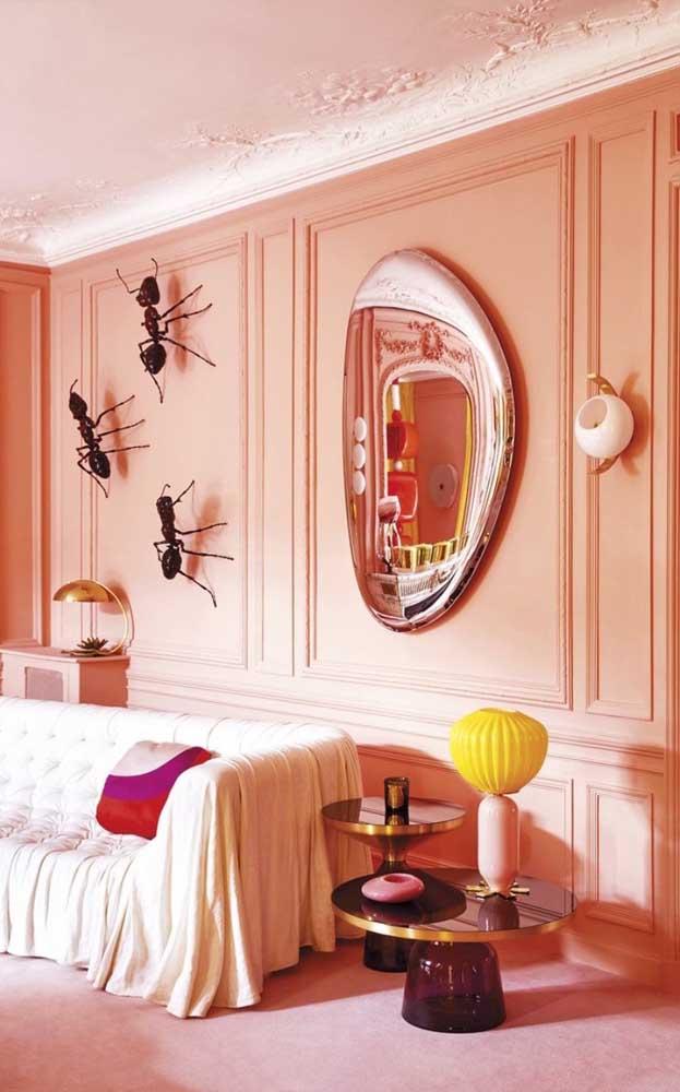 Essa sala de estar super conceitual apostou em um espelho bronze de formato inusitado para compor a decoração