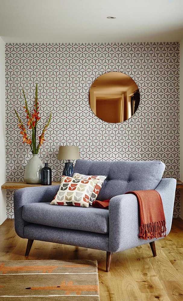 Sala de estar em tons terrosos e cinzas complementada pelo espelho de bronze na parede