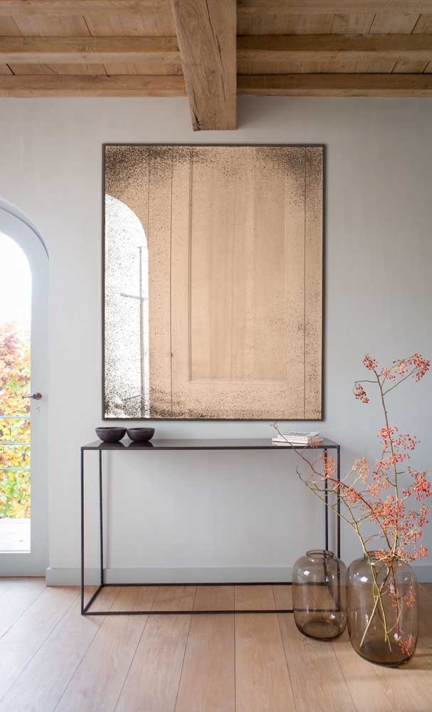 Espelho bronze e aparador na mesma sintonia nesse hall de entrada