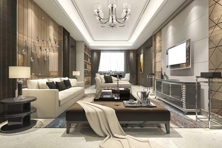 Essa sala ampla e espaçosa apostou no uso do espelho bronze como revestimento de parede
