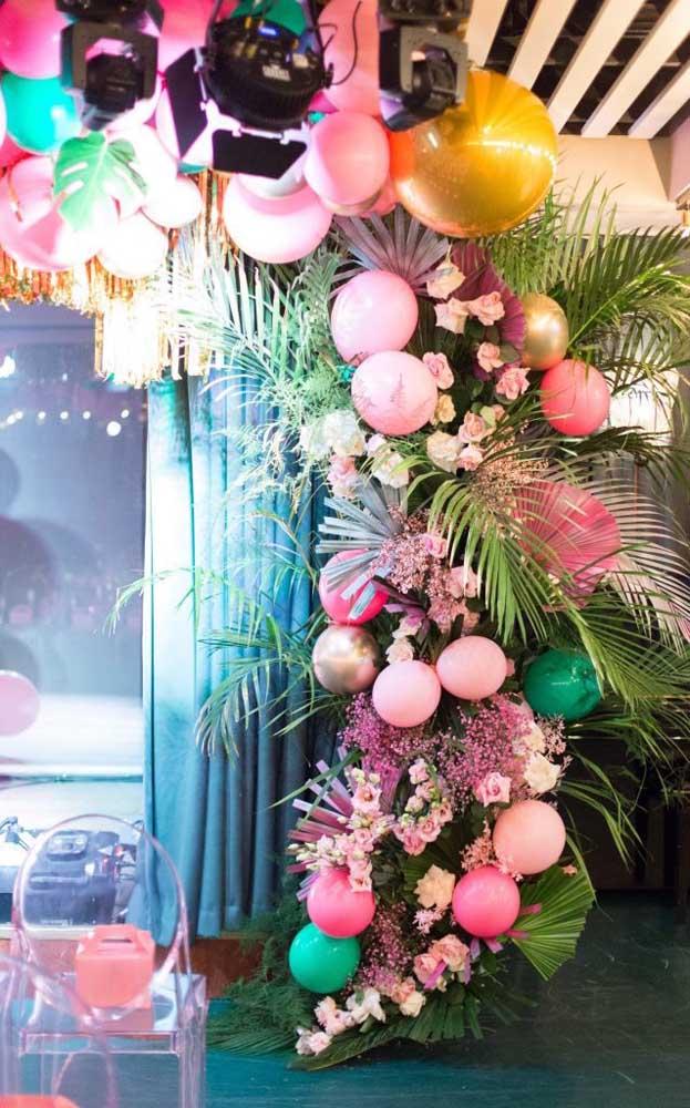 Para uma festa de inspiração tropical construa um arco de balões intercalado com flores e folhas