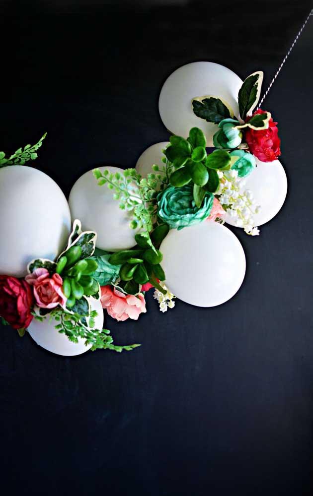 Diferente e original, esse enfeite de balões brancos traz ainda flores e suculentas artificiais para completar o arranjo